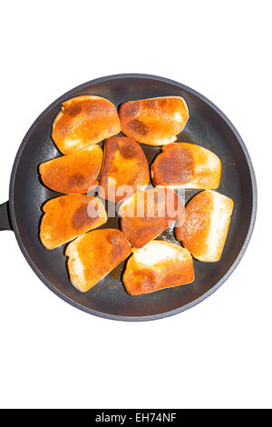 Picture of norwegian fish pudding slices in a frying pan - Stock Image