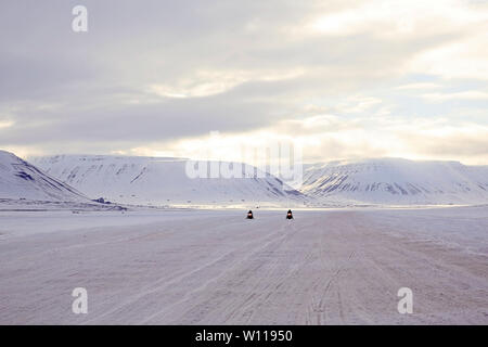 Two Snowmobiles Approaching, Snowy Mountains in the Background. Svalbard, Norway - Stock Image