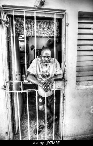 Afro Cuban man stood in doorway at home, Poor man, Poor Cuban, poverty Cuba, poverty Havana Cuba, leaning on gate, - Stock Image