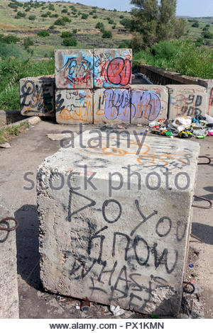 Ruined Bridge; Access restricted by concrete blocks covered in graffiti, 'Do you know what is free' painted on one. Israeli farmland on the other side - Stock Image