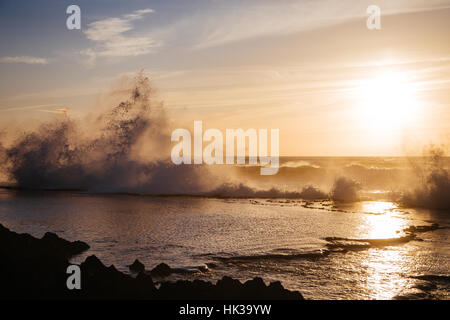 Big waves hitting the rocks as the golden sun sets on the coast of Hay El Fath, Rabat. Morocco - Stock Image