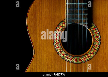 classical, acoustic guitar front closeup, strings, sound hole and soundboard, dark background, copy space, top view - Stock Image