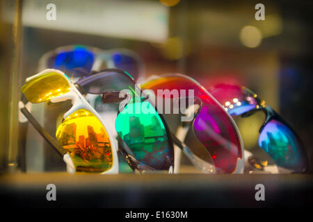Manhattan, New York, U.S. - May 21, 2014 - In the Oakley sunglasses store window display, 5 colorful sunglasses reflect the 7th Avenue buildings of midtown Manhattan. - Stock Image