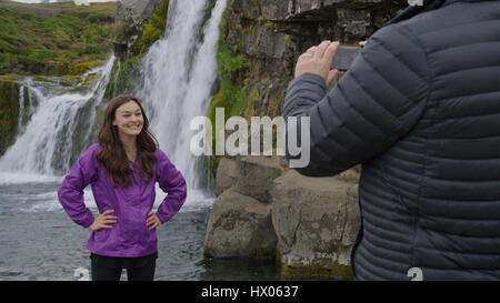 Man photographing smiling girlfriend posing near waterfall over remote rock cliffs - Stock Image
