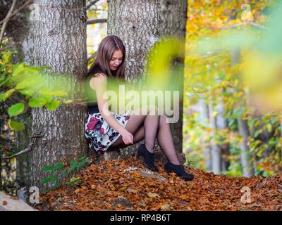 Nature-lover teen girl countrygirl legs tights sitting inclined on tree reaching down with hand - Stock Image