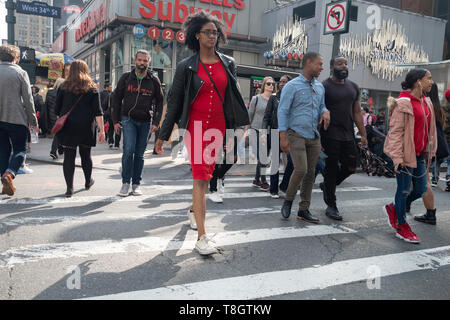A diverse group of pedestrians on 8th Avenue crossing West 34th Street near Penn Station in Manhattan. - Stock Image