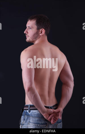 Rear view of a well-built bare-chested young man - Stock Image