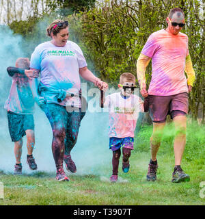 Family of two adults and two children being covered in paint on Macmillan cancer charity 5K color fun run. - Stock Image