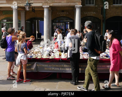 Tourists look at a stall selling antique bone china in Convent Garden,London, England - Stock Image