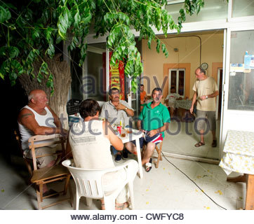 Greek men eating dinner at a village coffee shop villagers Greece people cafe eating - Stock Image