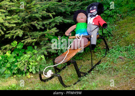 golliwog and brown doll soft toys sitting on small sledge  with christmas trees behind zala county hungary - Stock Image