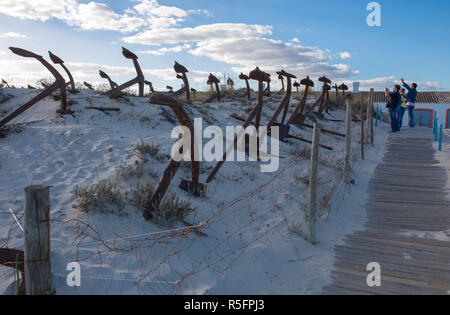 Tavira, Portugal - Oct 14th, 2018: Tourists taking pictures at Cemetery of Anchors. Memorial monument to dead fishermen of tuna industry in Portugal.  - Stock Image