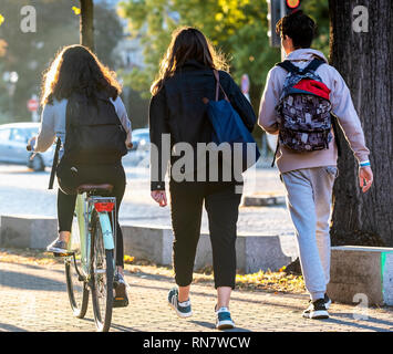 Strasbourg, Alsace, France, rear view of 2 teenagers walking and one girl biking on pavement, - Stock Image