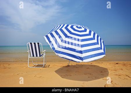 An umbrella and a chair on a sandy beach - Stock Image