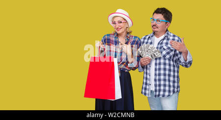 Happy family after shopping, adult man and woman in casual checkered shirt standing together,wife holding paper bag with toothy smile,husband fan of m - Stock Image