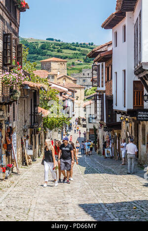 Santillana, Spain - 7th July 2018: Tourists walking up the street. The town has many historic buildings. - Stock Image