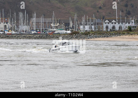 Leisure motor cruiser making its way up Conwy estuary to the open sea with the Conwy Marina in the background - Stock Image