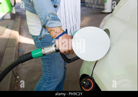 A woman is filling her car with fuel at a filling station - Stock Image