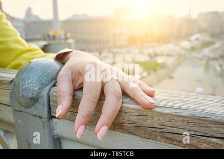 Closeup of hand mature 40, 45 year old woman, nails with manicure, ring on finger, outdoor. - Stock Image