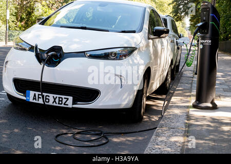 An electric car recharging via a roadside charge point in London, England, - Stock Image