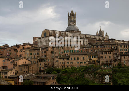 world heritage site Siena Italy skyline view with its magnificent medieval architecture and dome and ancient rooftops against a stormy sky - Stock Image