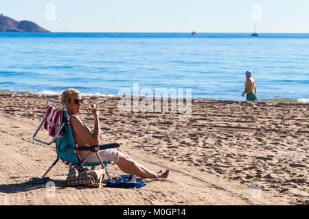 Poniente Beach, Benidorm, Costa Blanca, Spain. 22nd Jan, 2018. Winter sun in Benidorm, Spain.  Woman eating ice - Stock Image
