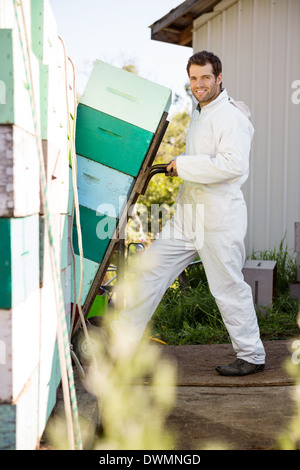 Beekeeper Smiling While Loading Stacked Honeycomb Crates In Truc - Stock Image