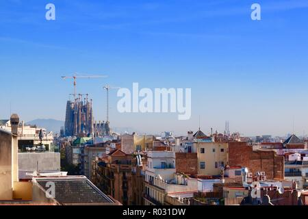 Barcelona, Spain, October 2018. View from the roof of Gaudi's Casa Mila also known as La Pedrera. The Sagrada Familia is visible in the distance. - Stock Image