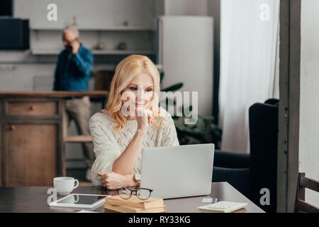 selective focus of pensive woman sitting near laptop with husband on background - Stock Image