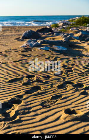 Footprints on the sandy beach with the sea in the background. - Stock Image