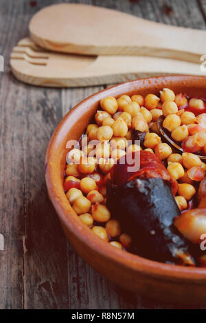 Chickpeas, sausage and bacon in a crockpot by wooden spoon and fork. Typical food from Madrid, Spain, with a rustic wooden board as a background. - Stock Image