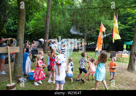 90th Kent County Show, Detling, 6th July 2019. A blue haired Fairy in woodland entertains children by blowing large bubbles.. - Stock Image