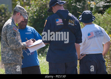 U.S. Army Sgt. Brandon Stafford assigned to the 133rd Military Police Company, S.C. Army National Guard, along with Mike Adams and Sergio Cueto from Virginia Task Force 1, Fairfax County, Va., converse with Clifton Harris of North Santee, S.C. during a health and welfare check October 6, 2015. The health and welfare checks were in response to widespread flooding in the area as a result of heavy rain. The South Carolina National Guard partnered with federal, state and local emergency management agencies and first responders. (U.S. Army National Guard photo by Sgt. Brian Calhoun/Released) - Stock Image