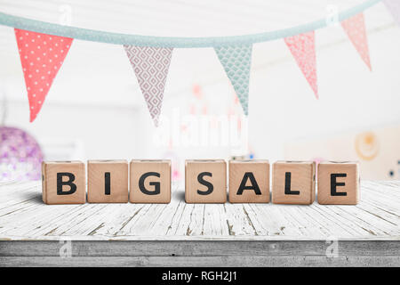Big sale sign on a white table with festive flags hanging above - Stock Image
