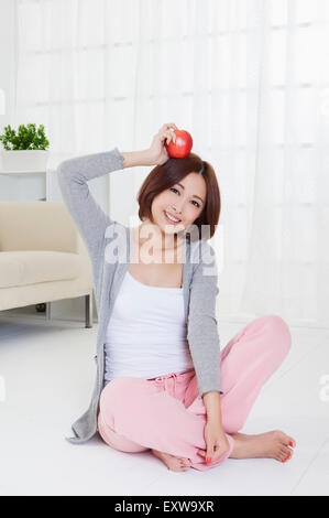 Young woman sitting on the floor and holding an apple, - Stock Image