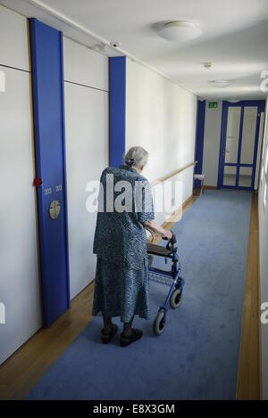 Betagte Altersheim-Insassin allein mit Gehhilfe - Solitary resident woman in home for the elderly with rolling walker - Stock Image