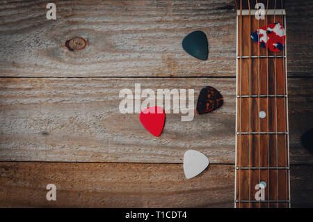 Acoustic guitar fretboard and some guitar picks on wooden table - Stock Image
