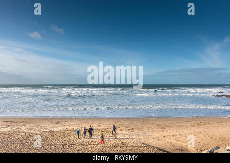 Children playing on the sand at Fistral Beach in Newquay in Cornwall. - Stock Image