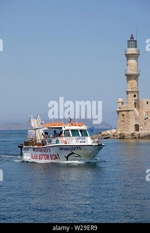 Chania, Crete, Greece. June 2019.  The lighthouse at the end of a long mole along the Old Venetian Harbour in Crete. Tour boat underway into the ancie - Stock Image