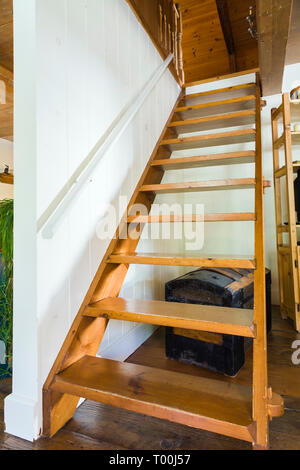 Pinewood Miller's stairs leading from living room to upstairs floor inside an old circa 1760 Canadiana fieldstone cottage style house - Stock Image