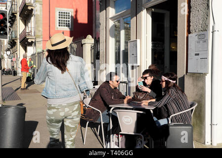 Group of friends customers sitting outside at a cafe restaurant table in the street in Porto, Portugal Europe EU   KATHY DEWITT - Stock Image