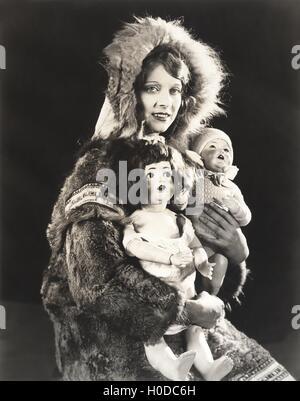 Women wearing Eskimo fur coat holding dolls - Stock Image