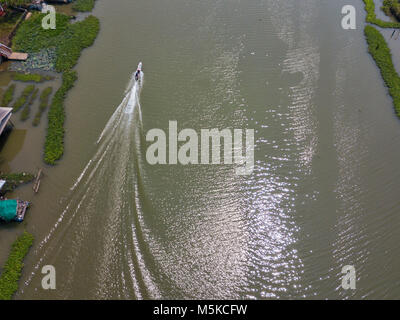 a long tail boat going up a river in Thailand, Southeast Asia - Stock Image