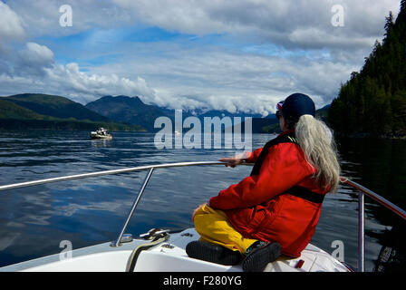 Female angler enjoying view sitting on bow of boat Davis Point Thurston Bay Campbell River BC Canada - Stock Image