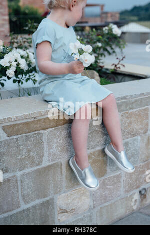 Girl with flowers sitting on wall - Stock Image