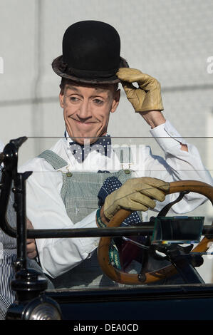 Chichester, West Sussex, UK. 14th Sep, 2013. Goodwood Revival. Goodwood Racing Circuit, West Sussex - Saturday 14th September. An actor dressed as Stan Laurel drives a vintage car whilst raising his trademark bowler hat to onlookers. Credit:  MeonStock/Alamy Live News - Stock Image