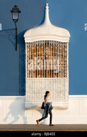 Woman passing colonial style window of the main square in Trujillo, Peru - Stock Image