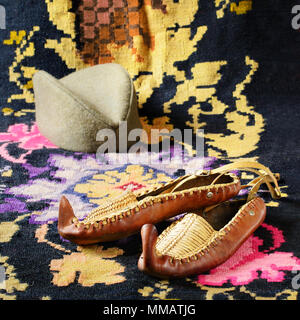 Opanci, leather folk shoes, a part of the Serbian national costume, are lying on a kilim. A Serbian folk cap (a shajkacha) is in a blurry background. - Stock Image