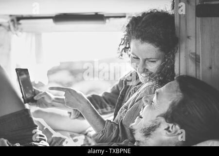 Happy couple watching on their mobile phone in minivan with wood interior - Man and woman using smartphone during their journey - Stock Image