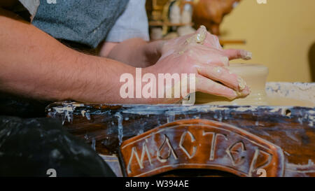 Professional male potter making ceramics in workshop - Stock Image